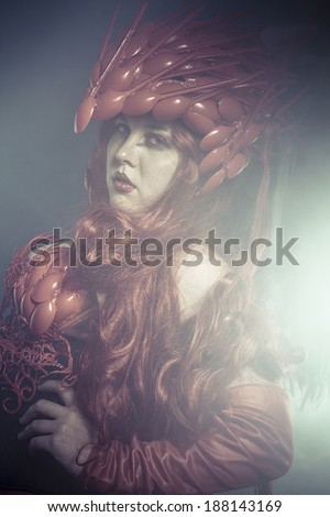 Beast, beautiful woman dressed in red armor dragon scales - stock photo