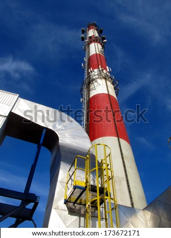 beat red high concrete chimney on blue sky background - stock photo