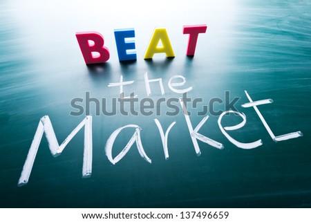 Beat the market, conceptual words on blackboard - stock photo