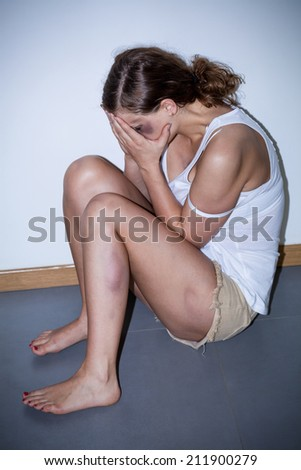 Beaten woman sitting on the floor, vertical