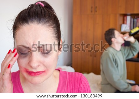 Beaten woman with bruises crying while her husband drinks alcohol, Stop violence against women, photography - stock photo