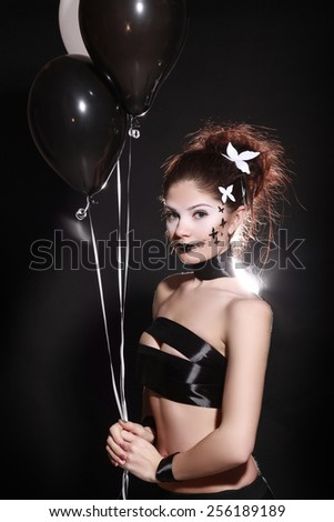 Beatiful girl with creative black make-up with butterflys. balloons