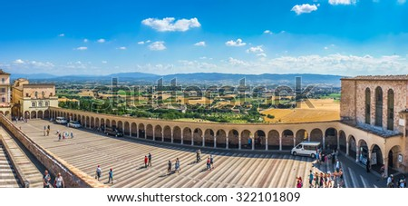 Beatiful panoramic view of Lower Plaza near famous Basilica of St. Francis of Assisi (Basilica Papale di San Francesco) in Assisi overlooking harvest fields and plains of Umbria, Italy - stock photo