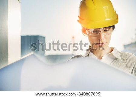 beatiful woman engineer is reviewing the plans of a construction work - stock photo
