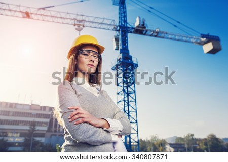 beatiful woman engineer is standing serious in front of a crane - stock photo