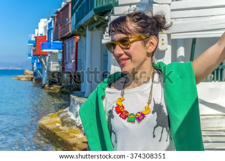 Beatiful young girl posing in front of little Venice in Mykonos, Greece during summer. - stock photo