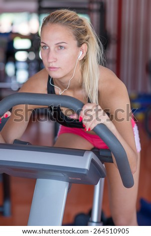 beatiful young woman doing sport spinning with headset in the gym - stock photo