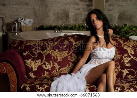 beatifull bride sitting on sofa - stock photo