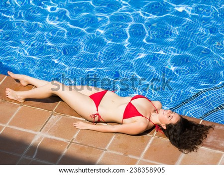 Beaty girl relax laying swimming pool and smiling on sunny day - stock photo
