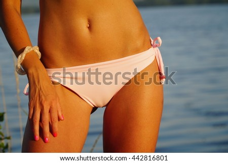 Beaufitul body of a girl's in bikini with summer lake