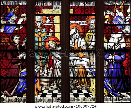 BEAUNE, FRANCE - APRIL 30: The stained glass window of Piety, with Chancelor Rolin and his wife Guigone de Salins, Saint Nicholas, and Saint Anthony the Great at Hotel Dieu in Beaune, France on April 30, 2012