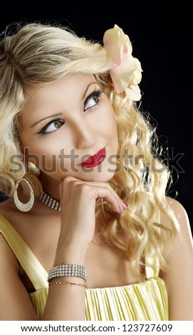 Beauteous curly blonde posing on a black background