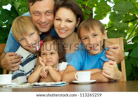 Beauteous family sitting on the veranda of his cottage - stock photo