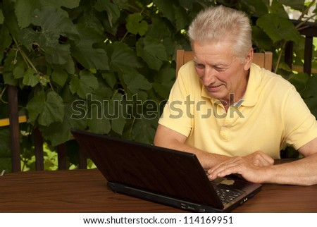 Beauteous older man sitting at a table at home on the veranda - stock photo