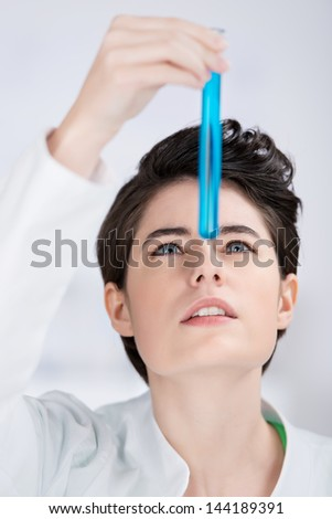 Beautfiul young laboratory technician testing a substance holding a test tube filled with a blue chemical solution up in front of her face as she watches for a reaction - stock photo