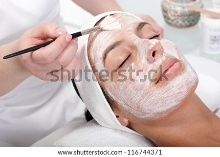 Beautician applying cream by brush on woman's face. - stock photo