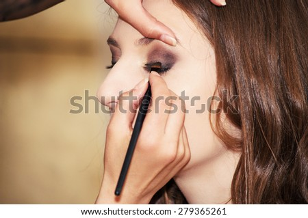 Beautician applying makeup on a model - stock photo