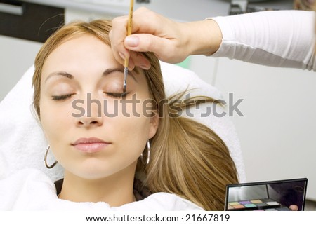 beautician applying makeup to a beautiful woman