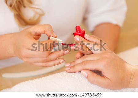 Beautician applying nail varnish in the salon while busy giving a female client a manicure