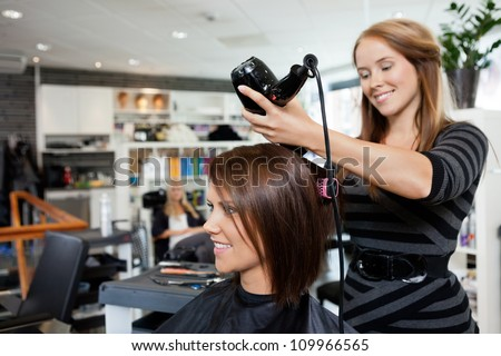 Beautician blow drying woman's hair after giving a new haircut at parlor - stock photo