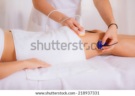 beautician conducts cosmetic procedures for body, beauty treatment for the skin thighs in a beauty salon