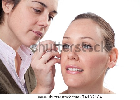 Beautician depilating a woman with tweezers