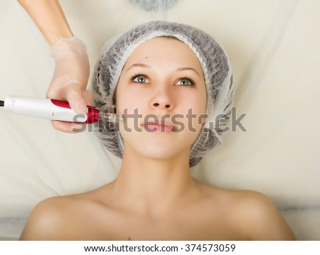 Beautician examining the face of a young female client at spa salon. fractional mesotherapy in a beauty salon. Professional consultation. - stock photo