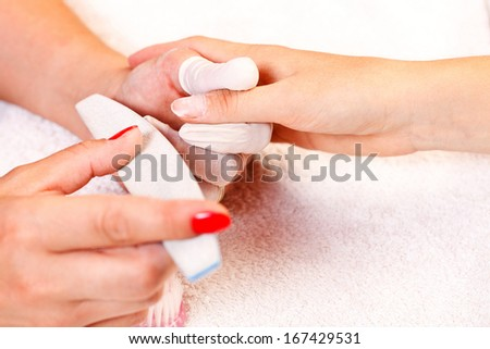 Beautician filing fingernails to a client in beauty salon.  - stock photo