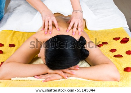 Beautician giving a back massage to a young woman at spa salon - stock photo