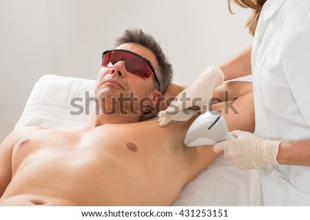 Beautician Giving Hair Removal Treatment To Mature Man In Beauty Saloon - stock photo