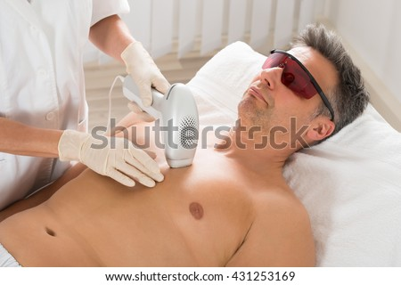 Beautician Giving Laser Epilation Treatment To Mature Man In Clinic - stock photo