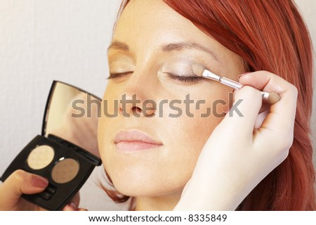beautician is doing make-up to red-haired woman - stock photo