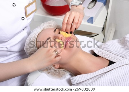 Beautician makes cleansing and exfoliating facial for beautiful girl. Beauty salon.