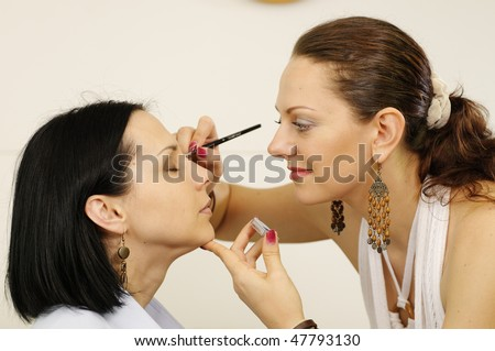 Beautician master is doing make-up to model girl - stock photo