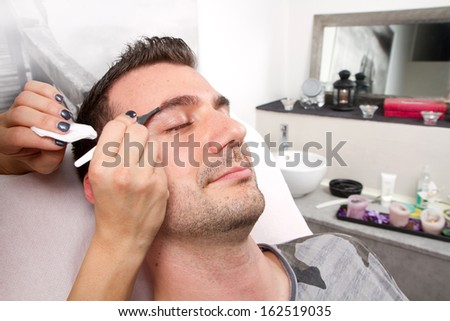 Beautician plucking a beautiful man eyebrows with tweezers in a beauty salon  - stock photo