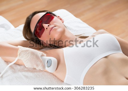 Beautician Removing Hair Of Young Woman's Armpit With Epilator - stock photo