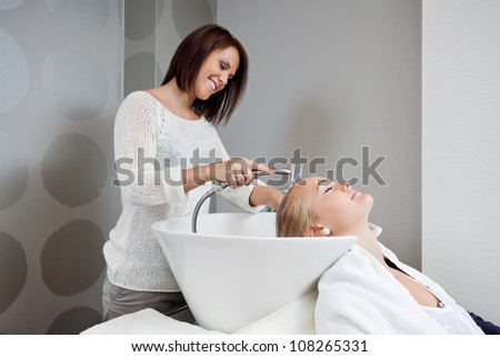 Beautician smiling while washing hair of female customer at beauty salon