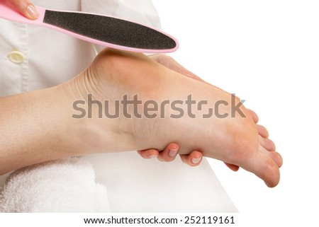 Beautician taking care of female client's foot giving pedicure treatment - stock photo