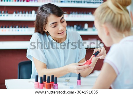 Beautician telling her client about nail polish in salon