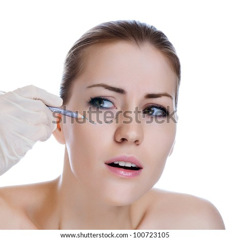 Beautician touch and draw correction lines on woman face. Before plastic surgery operetion. Isolated - stock photo