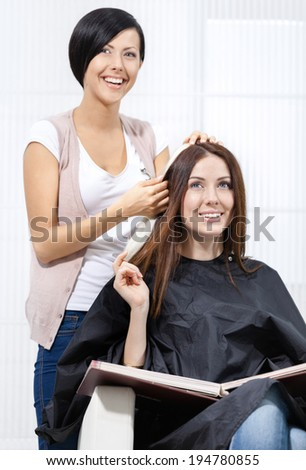 Beautician tries lock of dyed blond hair on the client sitting on the chair in the hairdressing salon
