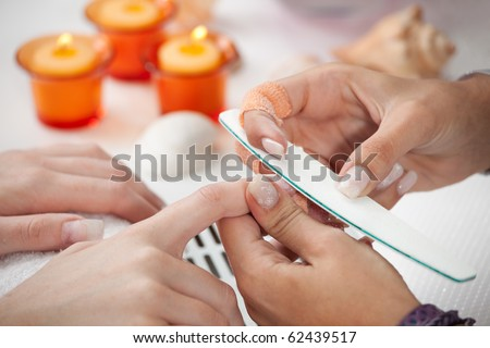 Beautician using nail file to prepare nails - stock photo
