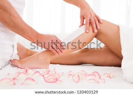Beautician waxing a woman leg applying a strip of material over the hot wax to remove the hairs when pulled - stock photo
