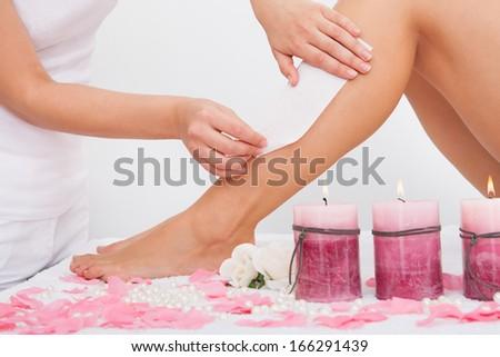Beautician Waxing A Woman's Leg Applying Wax Strip - stock photo