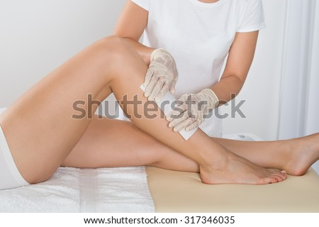 Beautician Waxing Leg Of Woman With Wax Strip At Beauty Clinic - stock photo