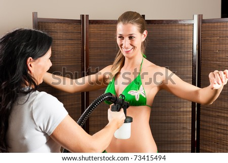 Beautician with airbrush-pistol and client in a cosmetic studio doing bronzing - stock photo