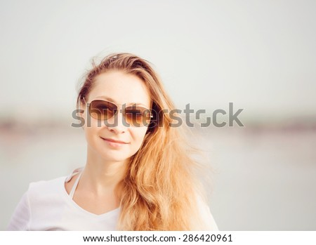 Beautifil young woman with long legs walking along the beach at sunset enjoing summer vacation - stock photo