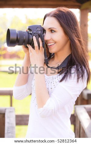 Beautifl smiling girl with camera on nature. - stock photo