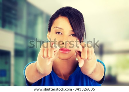 Beautifl young woman pointing on somebody. - stock photo