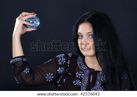 Beautifu black-haired witch holding the magic sphere in one hand - stock photo